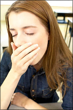 Teens need to sleep more. Teen girl student yawning.