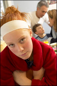 Adolescent development: Teen girl looking bored. Family in the background.