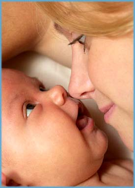 Attachment parenting: Cute picture of mother bonding with her infant.