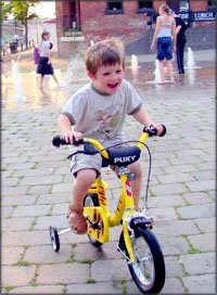 Child development stages of learning to bike and balance. Happy boy on bike with training wheels.