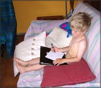 More concentration: Little boy sitting in sofa drawing.