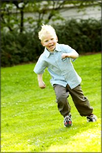 Little boy running on the grass.