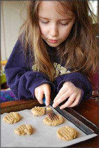 Taking on responsibility. Girl helping out in the kitchen, baking cookies