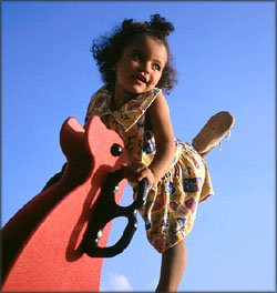 Little girl on playground with blue sky.