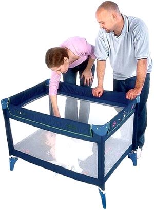 photo of parents, mom and dad, putting their baby to sleep in a crib