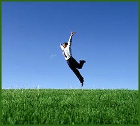 Freedom: Man jumping in joy in grass field.