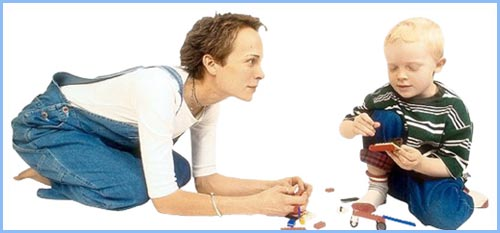 Mom giving son full presence. Picture of mom looking at her boy while playing with toys!
