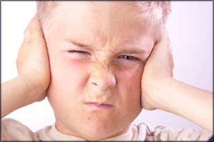 Stages of child development: Angry boy covering his ears.