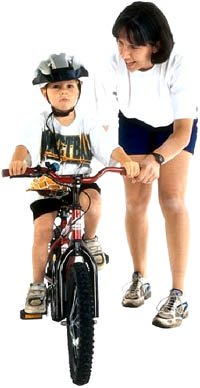 developmental milestones of biking: Boy on bike next to mom.